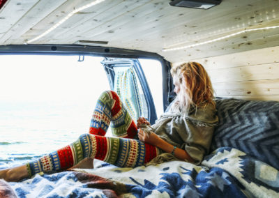 Woman looking at sea while leaning on mattress in travel trailer